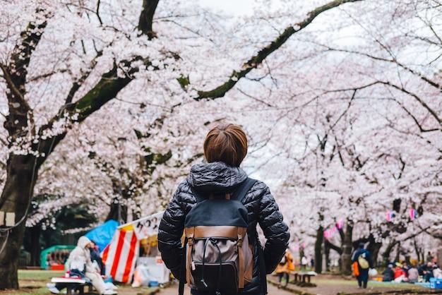 Viajante de mulher com mochila olhando incrível rosa e branco