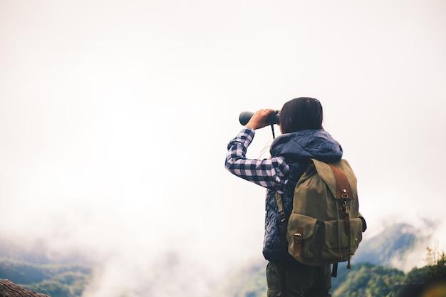 Viajante de mulher com mochila segurando o chapéu e olhando incríveis montanhas e floresta.