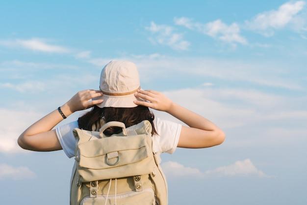 Viajante de mulher com mochila segurando o chapéu e olhando para o céu azul, conceito de viagens, espaço para texto e momento atmosférico