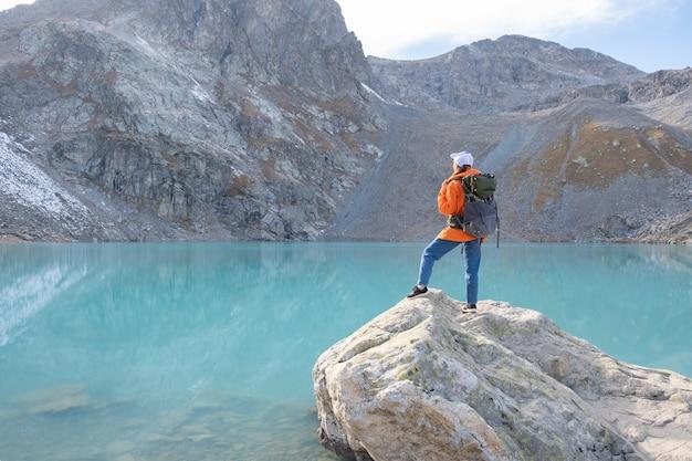 Viajante de mulher com uma mochila pesada em uma montanha de penhasco acima do lago. estilo de vida de viagens, aventura.
