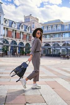 Viajante de mulher elegante e jovem hippie caminhando no centro de uma cidade europeia