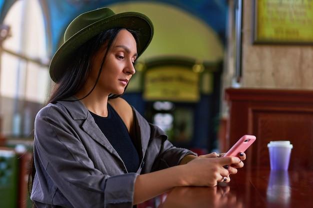 Viajante de mulher elegante elegante fofo atraente hipster usando um telefone durante um descanso em uma cafeteria