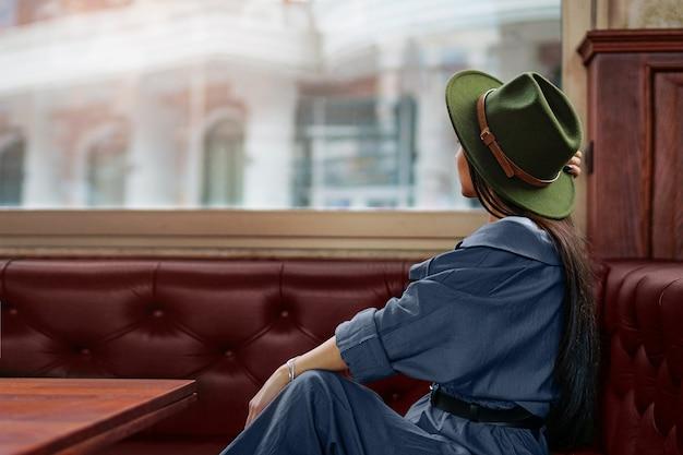 Viajante de mulher elegante pensativa, pensativo, hippie, sentada sozinha e olhando pela janela de um café