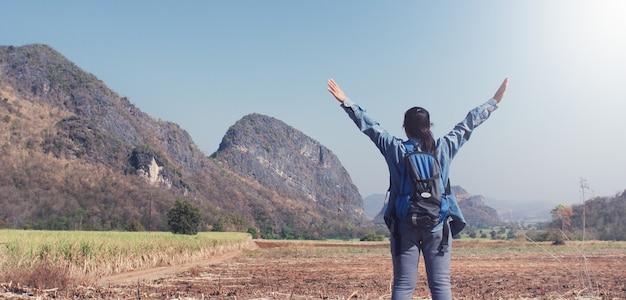 Viajante de mulher em pé liberdade com braços erguidos e desfrutando na bela natureza