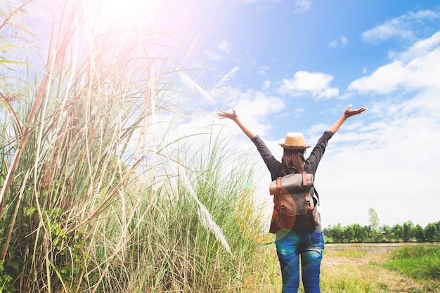Viajante de mulher empurra as mãos e respira no campo de gramíneas e céu azul, conceito de viagem wanderlust, espaço para texto