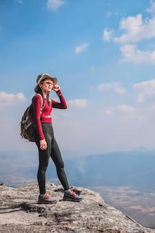 Viajante de mulher estão no topo da montanha e olhando para a natureza de férias.