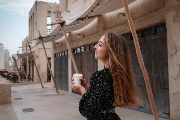 Viajante de mulher feliz com vestido preto, caminhando pelas ruas de uma antiga cidade ou vila árabe no meio do deserto. café em xícara branca, degustando o tradicional café árabe