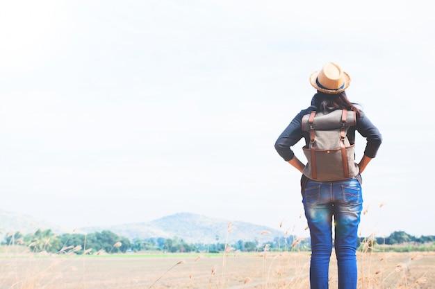 Viajante de mulher feliz olhando para o céu azul com fundo de montanha, conceito de viagem wanderlust, espaço para texto