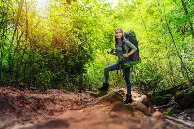 Viajante de mulher segurando a câmera com mochila em pé na floresta