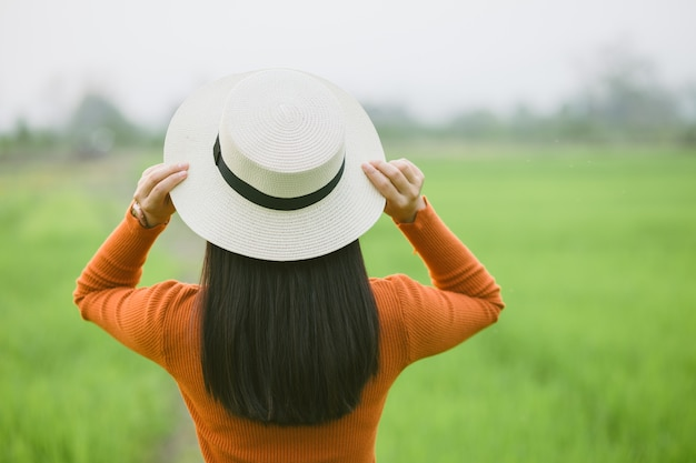 Viajante de mulher segurando o chapéu e olhando para o campo verde