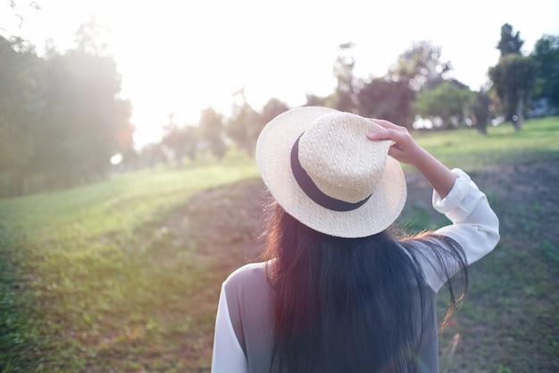 Viajante de mulher segurando o chapéu. olhando para a floresta.