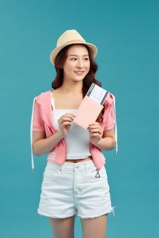 Viajante de mulher segurando o passaporte com o bilhete. retrato de menina feliz sorridente em azul.