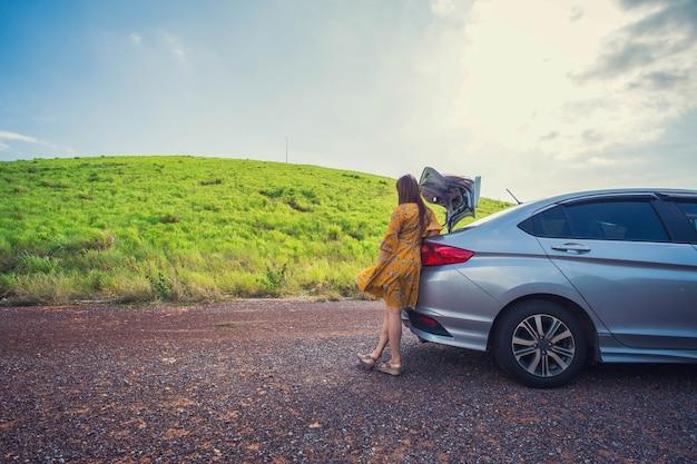 Viajante de mulher sentada no carro hatchback