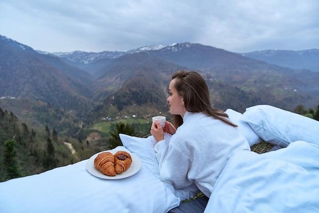 Viajante de mulher vestindo roupão de banho, apreciando o café da manhã de manhã cedo e a paisagem de vista da montanha durante o relaxamento na cama. momento calmo e tranquilo do conceito de desejo por viagens quando a pessoa sente felicidade e liberdade