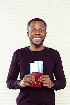 Viajante de negócios africano com bilhete e passaporte