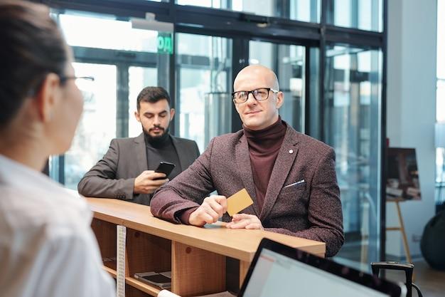 Viajante de negócios maduro e careca em trajes formais, mostrando um cartão de plástico para a recepcionista do hotel enquanto pede um quarto para a noite