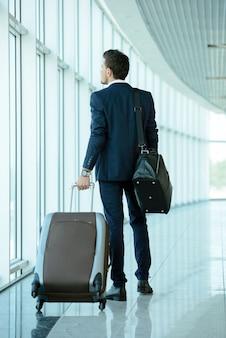 Viajante de negócios que puxa a mala de viagem e que guarda o passaporte.