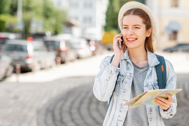 Viajante de tiro médio com mapa e telefone celular