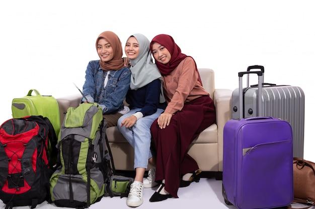 Viajante de três hijab segurando a mala quando está sentado no sofá