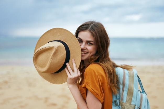 Viajante de verão feliz na praia perto do mar e chapéu na mão