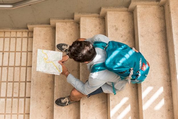 Viajante de vista superior sentado na escada