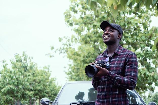 Viajante do homem africano está segurando a câmera e em pé perto de carro freelancing na estrada