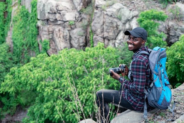 Viajante do homem africano sentado no penhasco e segurando a câmera com mochila