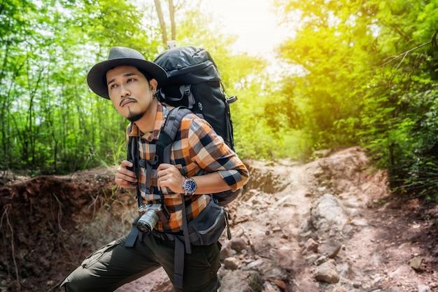 Viajante do homem com mochila, olhando para o lado andando na floresta