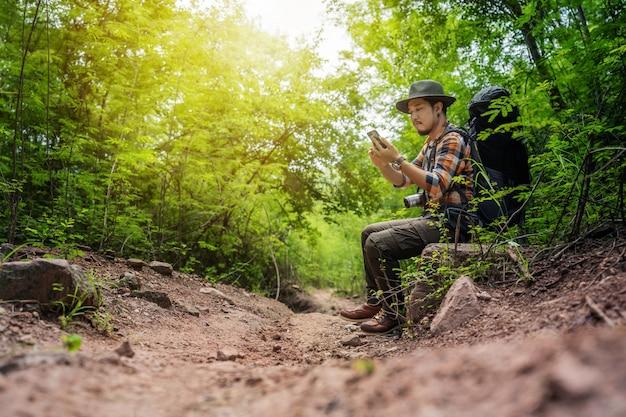 Viajante do homem com mochila usando smartphone na floresta