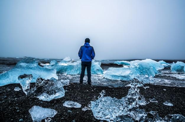 Viajante do homem em diamond beach na islândia.