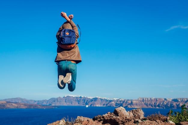 Viajante do homem pulando sentindo livre e feliz na ilha de santorini no outono. turista admirando a paisagem de vista da caldera