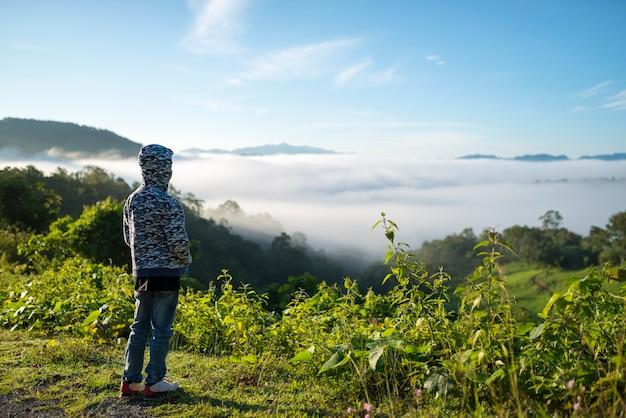 Viajante do jovem rapaz olhando o mar de névoa na luz da manhã.