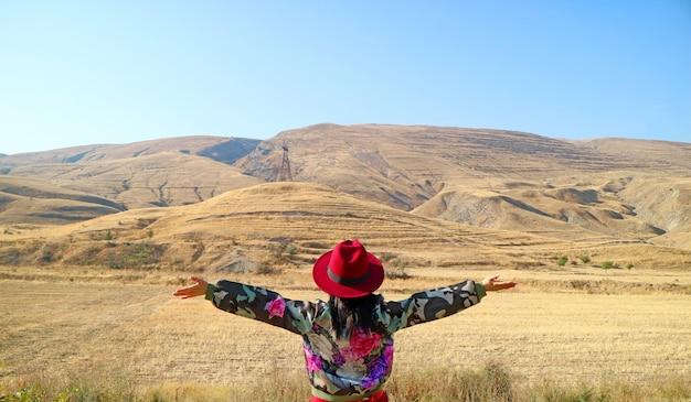 Viajante do sexo feminino, abrindo os braços com a impressionante paisagem da província de vayots dzor, armênia