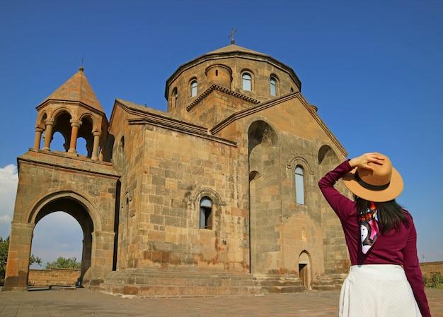 Viajante do sexo feminino impressionada com a igreja saint hripsime em vagharshapat, cidade da armênia