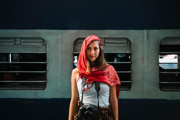 Viajante do sexo feminino ocidental em pé em uma estação de trem em varanasi