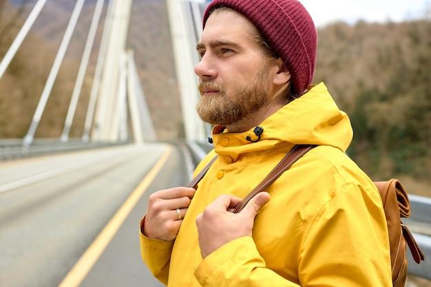 Viajante do sexo masculino caminhando na estrada de asfalto na ponte indo explorar o ambiente selvagem na primavera, cara hipster com mochila chegando às colinas durante uma viagem de carona