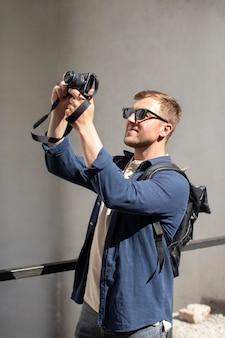 Viajante do sexo masculino com uma câmera em um lugar local