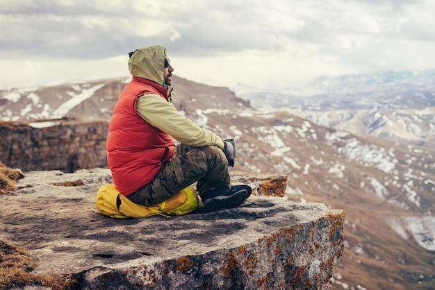 Viajante do sexo masculino com uma jaqueta vermelha senta-se na beira de um penhasco e aprecia a natureza da montanha