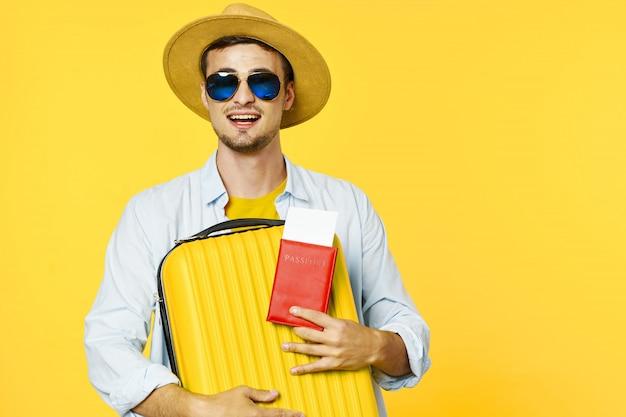 Viajante do sexo masculino com uma mala e passaporte