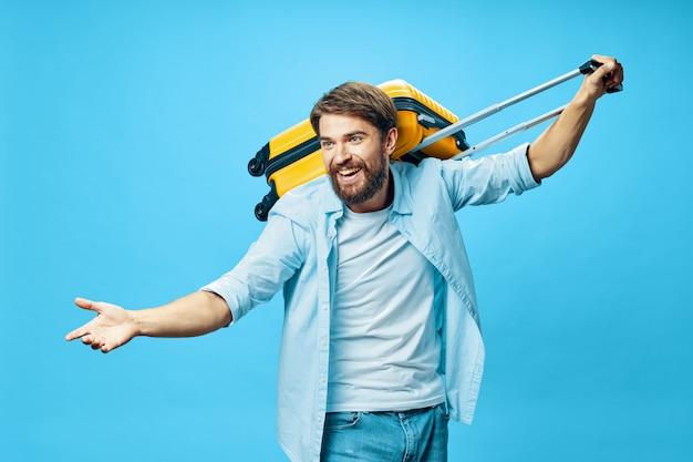 Viajante do sexo masculino com uma mala nas mãos posando em férias