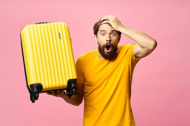 Viajante do sexo masculino com uma mala nas mãos posando, férias