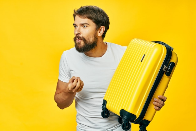 Viajante do sexo masculino com uma mala nas mãos posando no estúdio