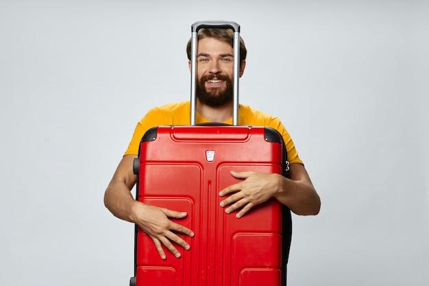 Viajante do sexo masculino com uma mala nas mãos posando
