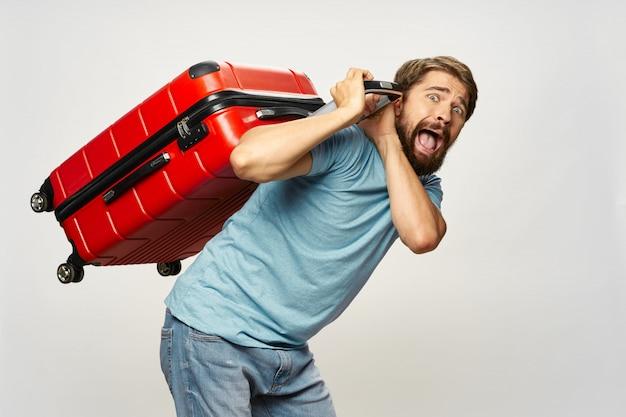 Viajante do sexo masculino com uma mala nas mãos