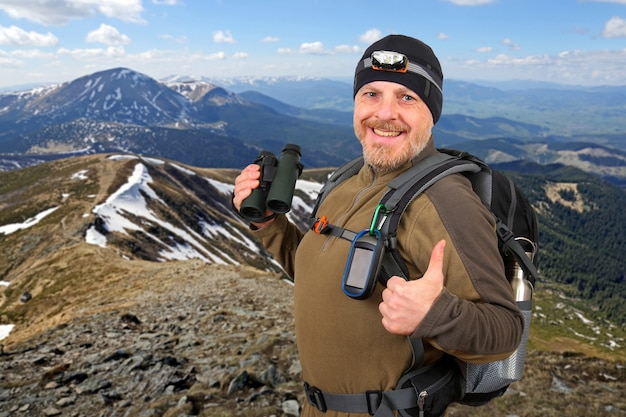 Viajante do turista feliz com binóculos na mão. bela montanha de neve ampla cordilheira