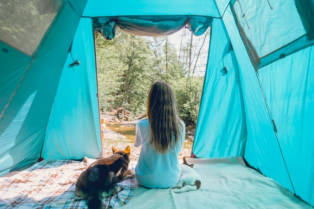 Viajante do turista feminino no acampamento em uma floresta com seus cães juntos em uma viagem na natureza.