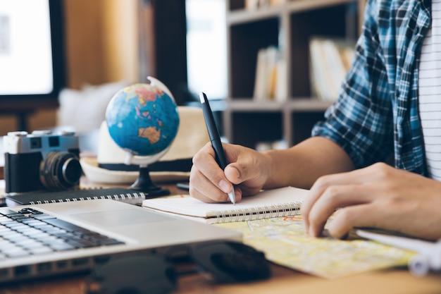 Viajante dos jovens que planeja a viagem de férias e a informação da escrita no caderno. planejando uma viagem, copie o espaço. fundo de viagens