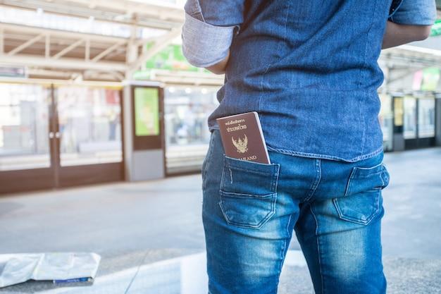 Viajante e passaporte tailandês em shorts jeans de bagagem