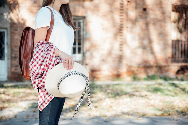 Viajante elegante com mochila vintage segurando o chapéu