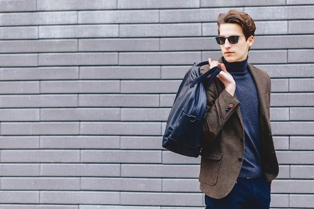 Viajante elegante em jaqueta com passaporte e bilhetes em contexto urbano